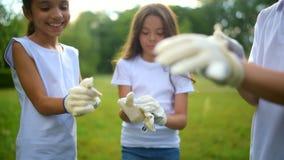 Śliczni mali ekolodzy stawia na rękawiczkach dla zgłaszać się na ochotnika w parku zbiory wideo