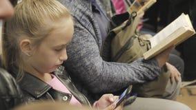 Śliczni nastoletni dziewczyn spojrzenia w ona telefon podczas gdy siedzący w metrze Dziecko używa internet szukać dla informacji zbiory