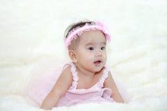 Śliczni pięć miesięcy azjatykciego dziecka śmia się z menchiami ubierają Obraz Stock