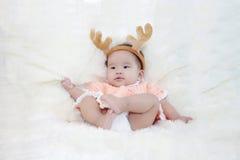 Śliczni pięć miesięcy azjatykciego dziecka w reniferowych rogach , na jaskrawym miękkim dywanie zdjęcie stock