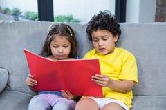 Śliczni rodzeństwa czyta książkę na kanapie fotografia stock