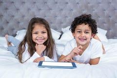Śliczni rodzeństwa używa pastylkę na łóżku obrazy royalty free