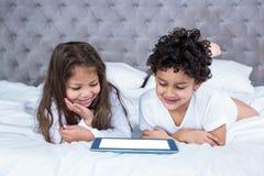Śliczni rodzeństwa używa pastylkę na łóżku obraz stock