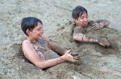Śliczni szczęśliwi nastoletni chłopacy bawić się w piasku obraz royalty free