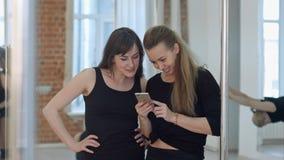 Śliczni szczęśliwi słupów tancerze bierze przerwę od ich treningu i socjalny networking z telefonem komórkowym Fotografia Stock