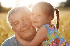 Śliczni uśmiechnięci mali dziewczyna uściski z wielkim kochają jej dziadu, być dziękczynni dla niezapomnianego dnia, patrzeją joy obrazy stock