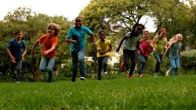 Śliczni ucznie ściga się na trawy outside szkole