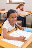 Śliczni ucznie rysuje przy ich biurkami jeden ono uśmiecha się przy kamerą Zdjęcie Stock