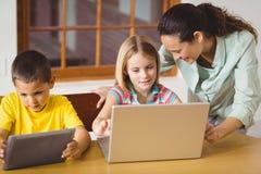 Śliczni ucznie w klasowym używa laptopie i pastylce z nauczycielem fotografia stock