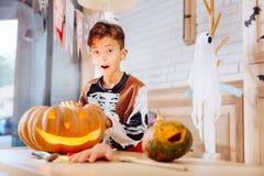 Śliczny śmieszny chłopiec czuć excited podczas gdy trwanie pobliska rzeźbiąca Halloweenowa bania obrazy royalty free