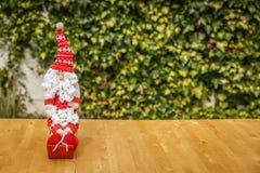 Śliczny Święty Mikołaj na drewnianym stole z zielonym tłem Obraz Stock