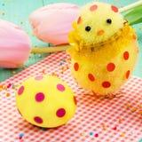Śliczny żółty Easter kurczątko, Easter jajko w polek kropkach na czerwonej pielusze Obraz Stock