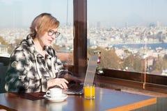 Śliczny żeński Freelancer pracuje na komputerze przy dachu wierzchołka kawiarnią zdjęcia stock