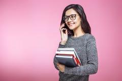 Śliczny żeńskiego ucznia mienie rezerwuje gdy opowiadający na telefonie na różowym tle zdjęcia stock