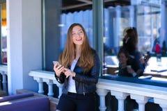Śliczny żeńskiej osoby gawędzenie smartphone przy uliczną kawiarnią Zdjęcie Royalty Free