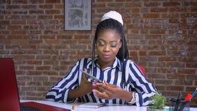 Śliczny afrykański żeński seans zieleni ekran z uśmiechniętą twarzą podczas gdy siedzący przy jej pracującym biurkiem z ceglanym
