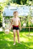 Śliczny aktywny dzieciak chłopiec doskakiwanie w ogródzie na ciepłym pogodnym letnim dniu Szczęśliwy dzieciak patrzeje kamerę Uro zdjęcia stock