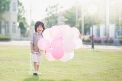Śliczny Azjatycki dziecko z dużo szybko się zwiększać bawić się w parku pod su Fotografia Royalty Free