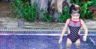 Śliczny azjatykci żeński berbecia dziecko podczas gdy pływający i bawić się na basenie obrazy stock