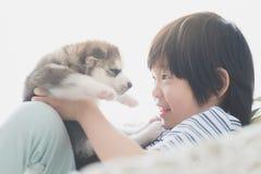 Śliczny azjatykci dziecko bawić się z siberian husky szczeniakiem Fotografia Royalty Free