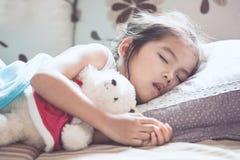 Śliczny azjatykci dziecko dziewczyny dosypianie i przytulenie jej miś Obraz Royalty Free