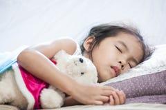 Śliczny azjatykci dziecko dziewczyny dosypianie i przytulenie jej miś Fotografia Royalty Free