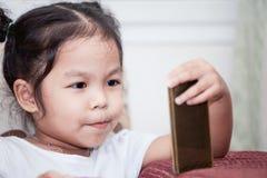 Śliczny azjatykci dziecko dziewczyny obsiadanie na kanapie i używać mądrze telefon Obraz Royalty Free