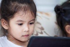 Śliczny azjatykci dziecko dziewczyny obsiadanie na kanapie i używać mądrze telefon Obrazy Royalty Free