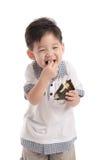 Śliczny azjatykci dziecko je ryżową piłkę lub onigiri Obrazy Royalty Free