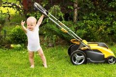 Śliczny berbeć z lawnmower tnącą trawą Obrazy Stock