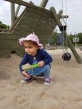 Śliczny berbeć z różowym kapeluszem i błękit suknią bawić się w piasku Fotografia Royalty Free