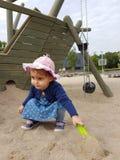 Śliczny berbeć z różowym kapeluszem i błękit suknią bawić się w piasku Zdjęcie Royalty Free