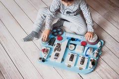 Śliczny berbecia dziecko bawić się z ruchliwie deską w domu Fotografia Royalty Free
