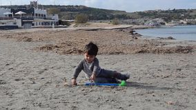 Śliczny berbecia obsiadanie w piasku i bawić się z klingerytu golfa piaskiem na plaży i kijem zbiory