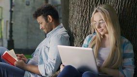 Śliczny biracial facet spogląda przy blondynki dziewczyną z laptopem z czułością i miłością zbiory