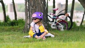 Śliczny blondynki dziewczyny obsiadanie pod drzewnym jest ubranym rowerowym hełmem zdjęcie wideo
