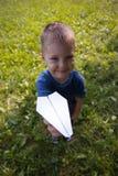 Śliczny caucasian dziecko bawić się papierowego samolot w parku outdoors w lato słonecznym dniu zdjęcie stock