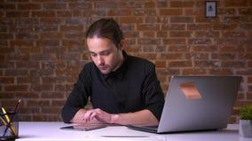 Śliczny caucasian facet scrolling jego pastylkę podczas gdy siedzący przy jego pracującym miejscem z ściana z cegieł behind