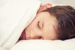 Śliczny chłopiec dosypianie pod koc w łóżku w sypialni Kłamać o zdjęcie stock