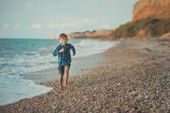 Śliczny chłopiec dzieciaka dziecko jest ubranym elegancką koszula i niebieskich dżinsów bosego pozuje biegać na kamień plaży z ws Obraz Stock