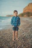 Śliczny chłopiec dzieciaka dziecko jest ubranym elegancką koszula i niebieskich dżinsów bosego pozuje biegać na kamień plaży z ws Zdjęcia Stock