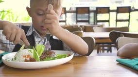 Śliczny chłopiec i dziewczyny łasowania jedzenie w dzieciakach restauracyjnych Małej dziewczynki i chłopiec łomotanie w restaurac zbiory