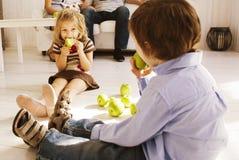 Śliczny chłopiec i dziewczyny łasowanie zielenieje jabłka w domu Obraz Royalty Free