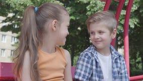 Śliczny chłopiec i dziewczyny obsiadanie na huśtawkowym zakończeniu w w górę parka, patrzeje each inny z czułością Kilka szczęśli zbiory