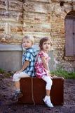 Śliczny chłopiec i dziewczyny obsiadanie na walizce Fotografia Royalty Free