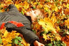 Śliczny chłopiec lying on the beach na żółtych liściach, jesieni pojęcie Zdjęcie Stock