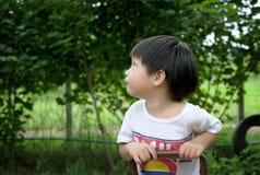 Śliczny chłopiec obsiadanie i patrzeć na seesaw obraz stock