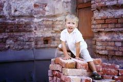Śliczny chłopiec obsiadanie na cegłach Obraz Stock