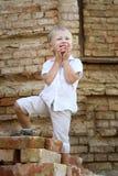 Śliczny chłopiec obsiadanie na cegłach Obrazy Royalty Free