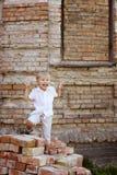 Śliczny chłopiec obsiadanie na cegłach Obraz Royalty Free